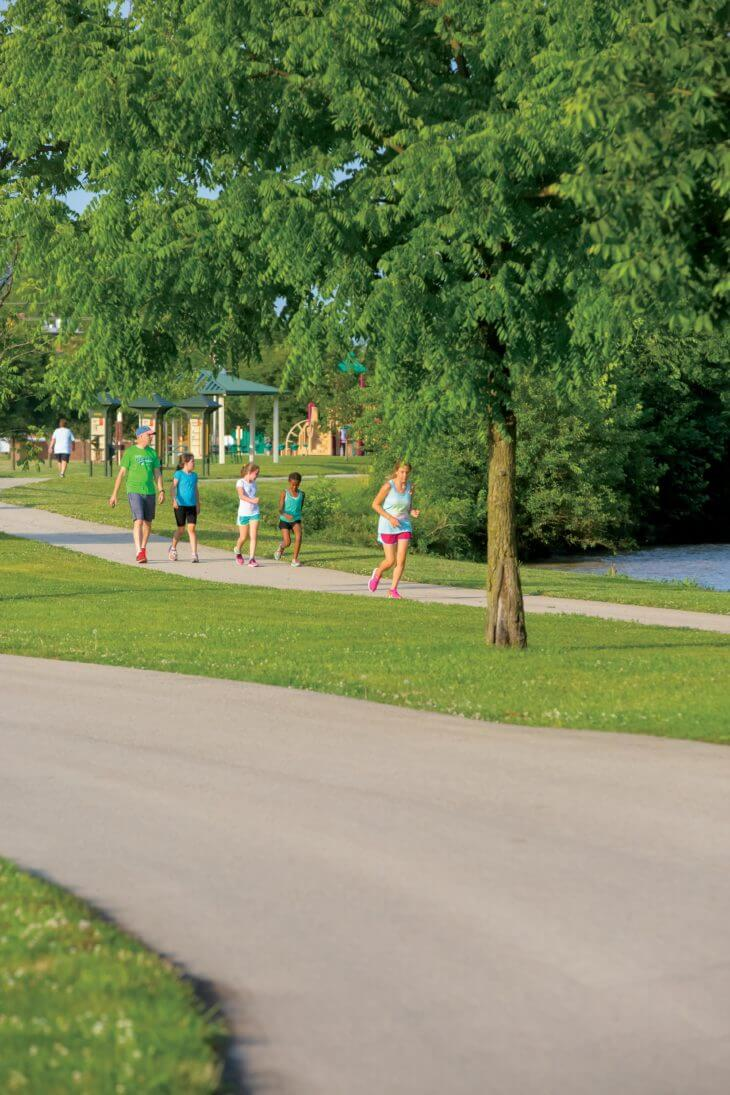 Woman jogging near park on greenway trail with father and kids behind her in Yorktown, Indiana