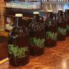 Growlers lined up on bar of Creatures of Habit Brewery in Anderson, Indiana