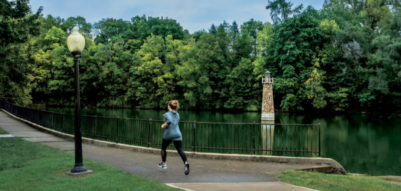 Woman jogs along Fall Creek in Pendleton, Indiana