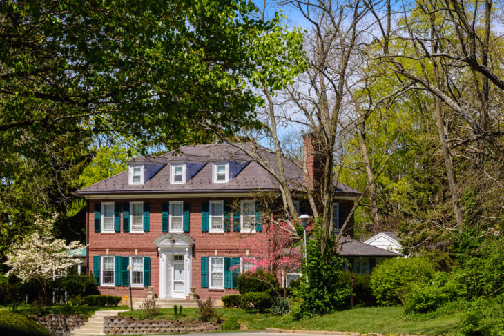 A two story brick home with green shutters in the Reeveston neighborhood of Richmond, Indiana