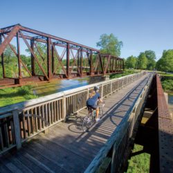 Woman on bicycle on a bridge across a bridge which crosses the White River along the Cardinal Greenway in Muncie, Indiana
