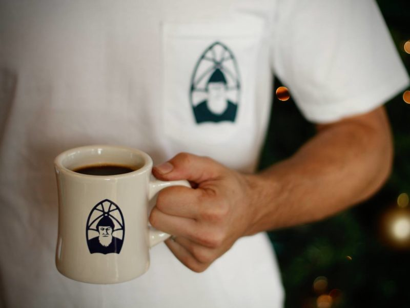 Man holding a mug of coffee at The Abbey in Marion, Indiana