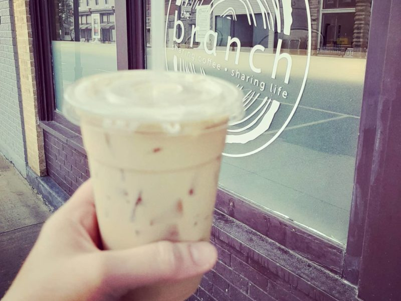 Person holding up an iced latte outside of The Branch in Fairmount, Indiana