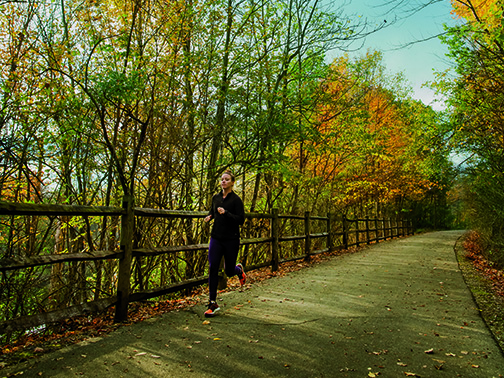 Woman jogging along the Cardinal Greenway in the Fall in East Central Indiana