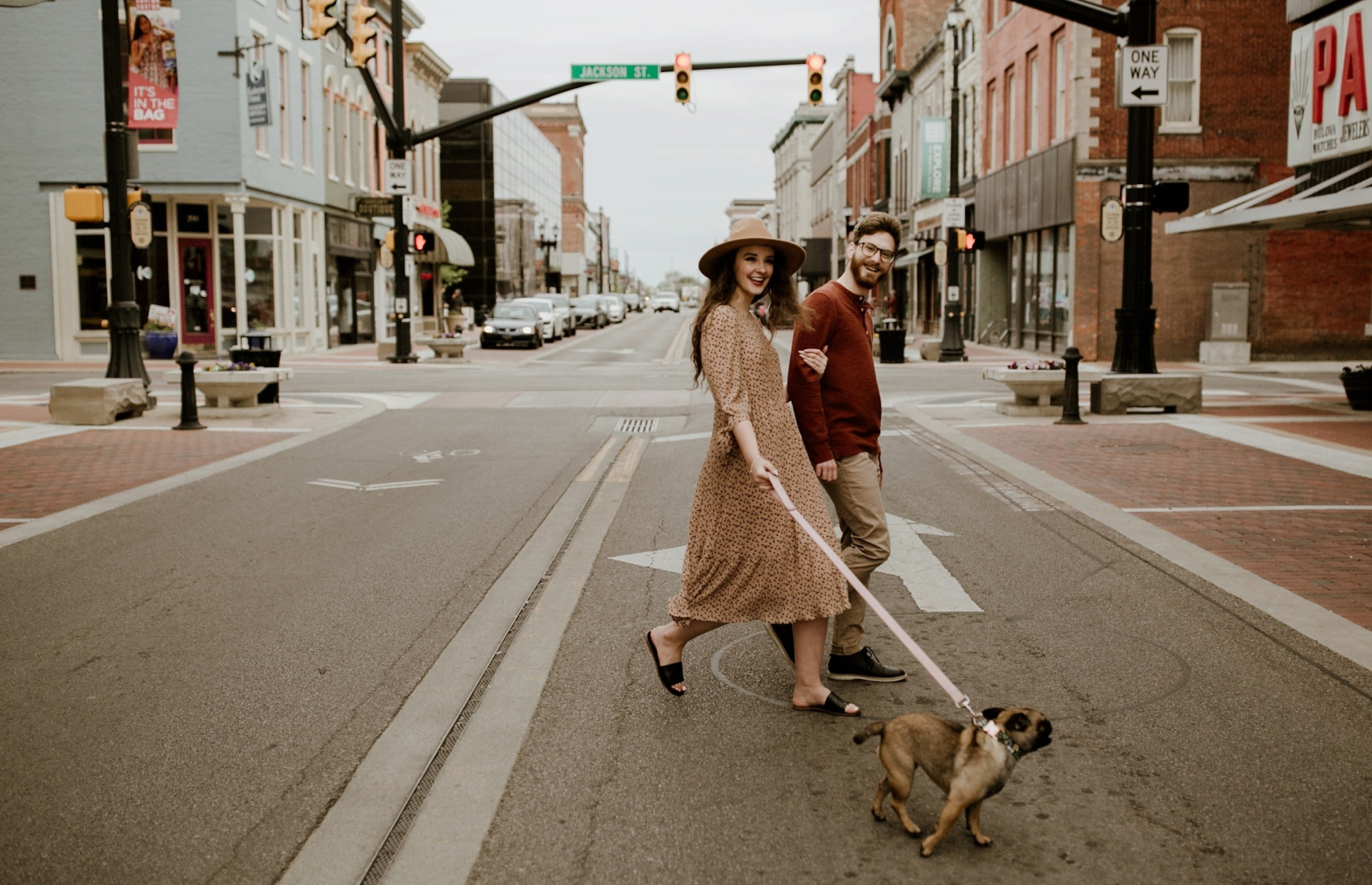 Courtney Thomas and fiancé walking across the street with a dog in downtown Muncie, Indiana