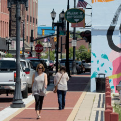Woman walking downtown Muncie, Indiana near a colorful mural on the side of a building