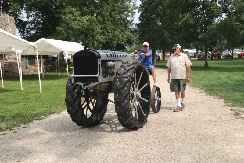 Man walking beside man driving tractor at the Tri-State Antique Gas Engine Tractor Show in Portland, Indiana